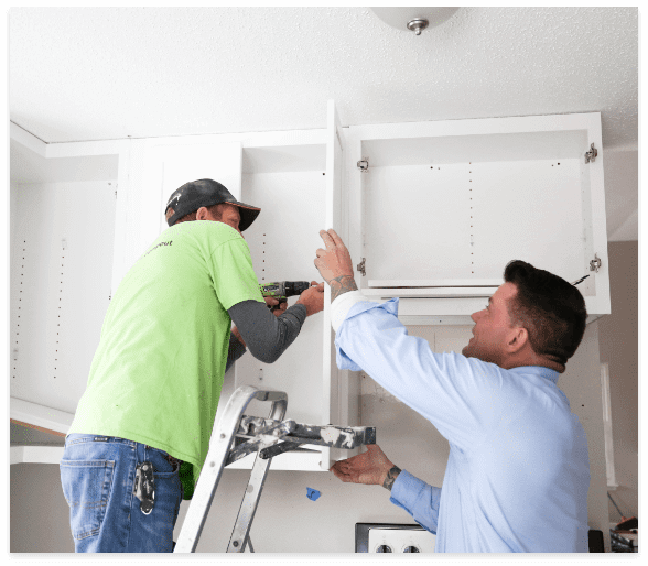 man drilling into cabinet